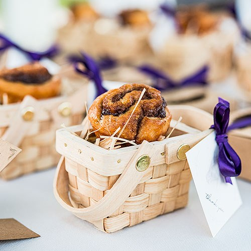 Miniature Woven Picnic Basket with cinnamon bun and tag tied with purple ribbon