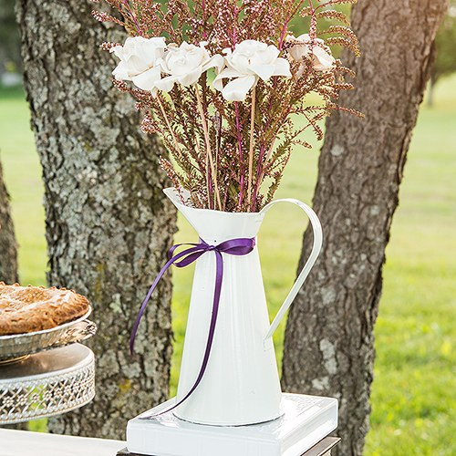 White enamel pitcher with wild flowers and purple ribbon on outdoor table.